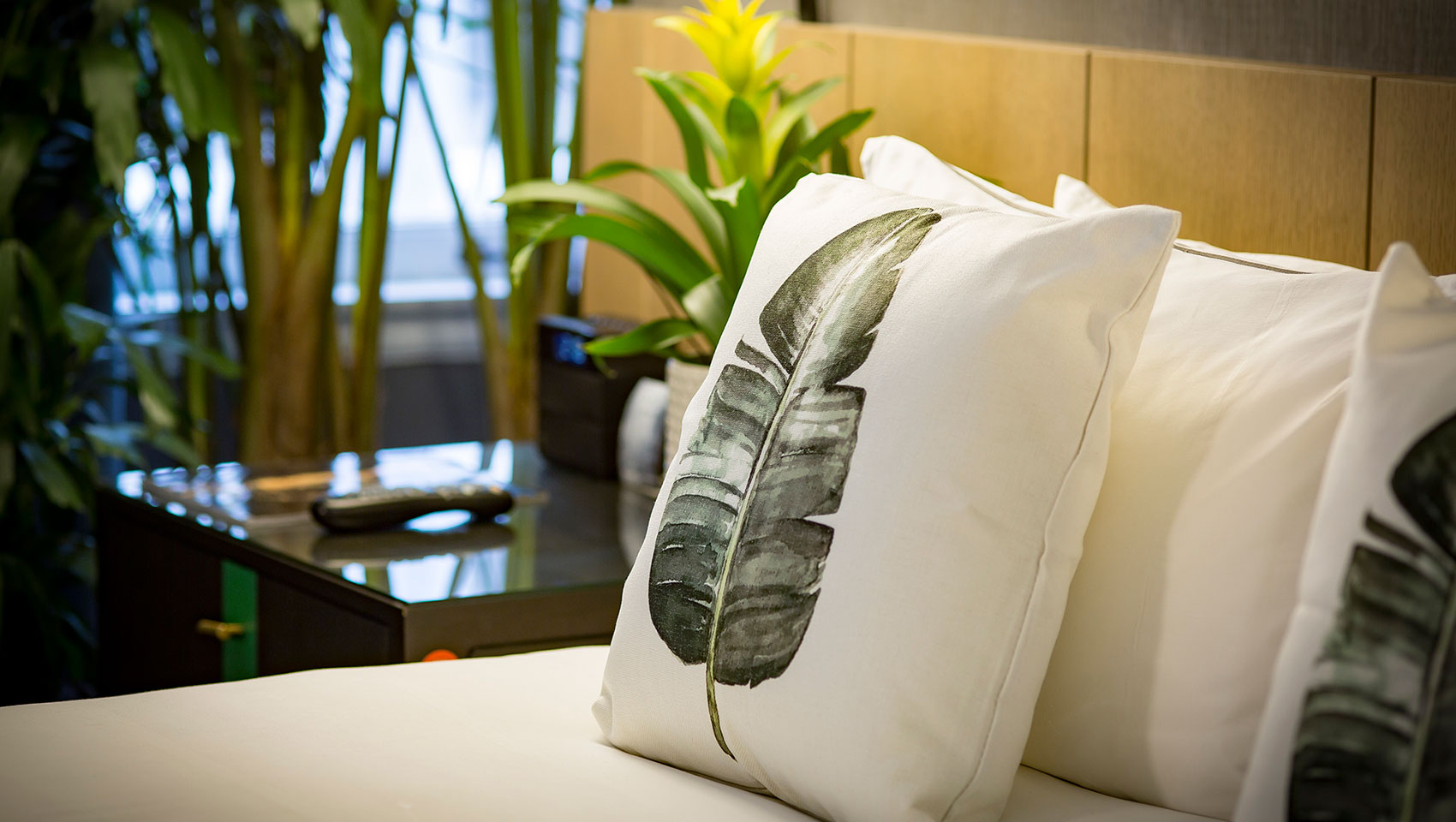 throw pillow on bed with picture of palm leaf