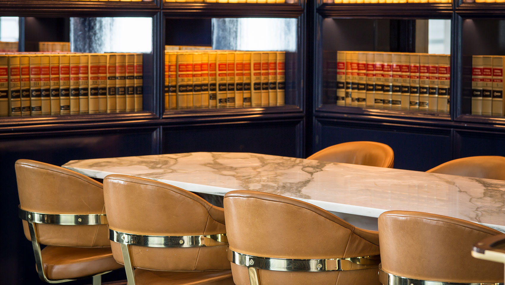 Marble table with leather seating, Bookshelf with leather bound books