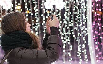 Girl taking photos of holiday lights on smartphone